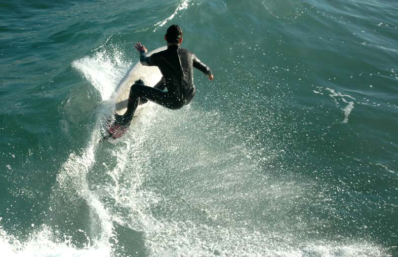Surfer riding a wave without a surf helmet